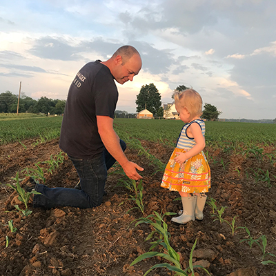 Katie's husband and daughter checking the corn crop on their family farm.