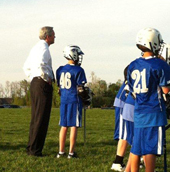 Brent helping no. 46 with his lacrosse game.